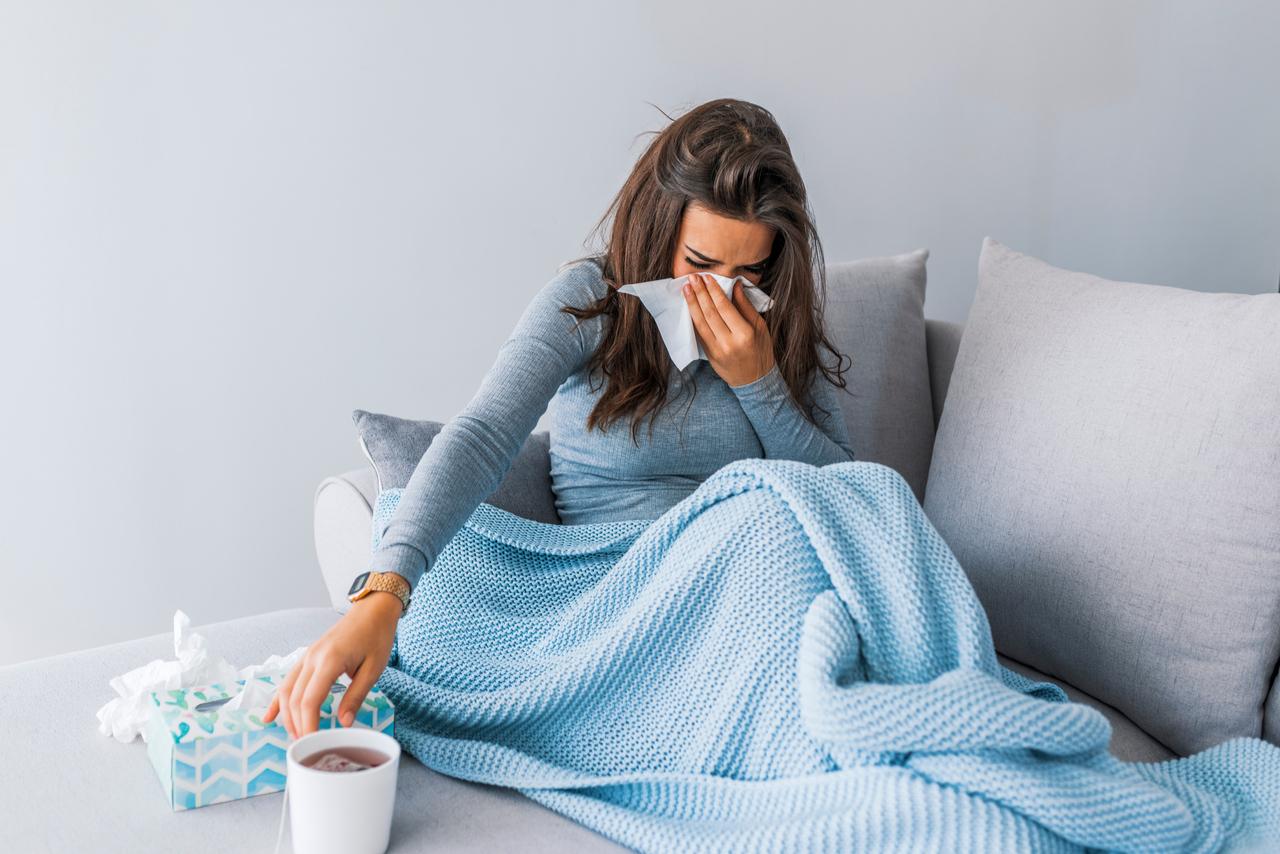 chora kobieta leżąca w łóżku z chusteczkami i lekami